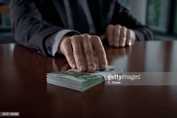businessman putting euro bills on table - bestechung stock-fotos und bilder