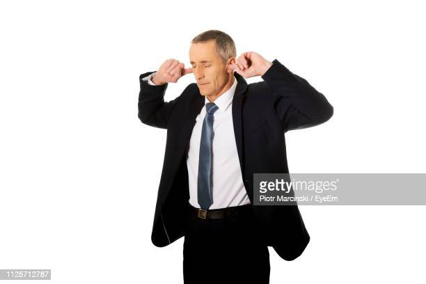 businessman putting fingers in ears against white background - fingers in ears stock pictures, royalty-free photos & images