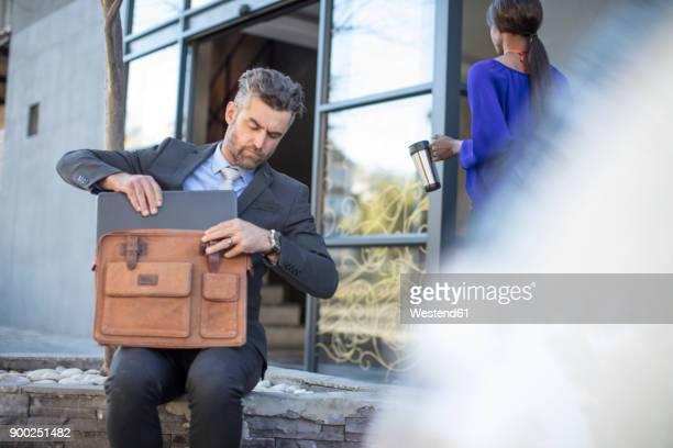 Businessman putting his laptop into his bag