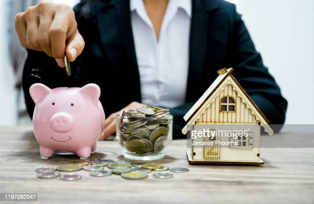 businessman putting money coins into a pink piggy bank thinking of buying a new house - saving money for future concept and loan for plan business investment for real estate in the future concept. - erschwinglich stock-fotos und bilder