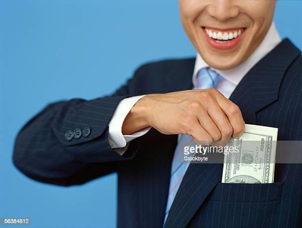 businessman putting money into his pocket