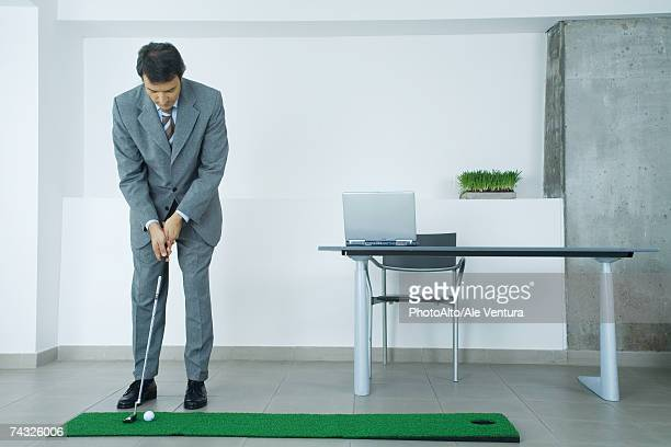 businessman putting on artificial turf in office - wasting time stock pictures, royalty-free photos & images
