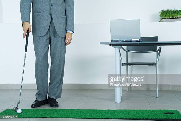 Businessman putting on artificial turf in office