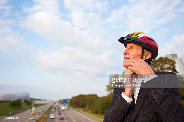 Businessman putting on bicycle helmet