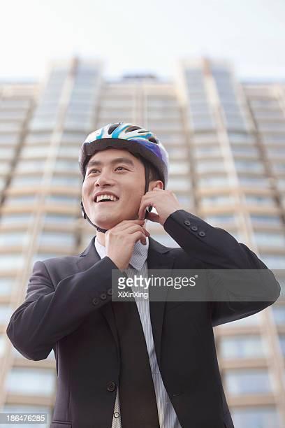 Businessman putting on cycling helmet