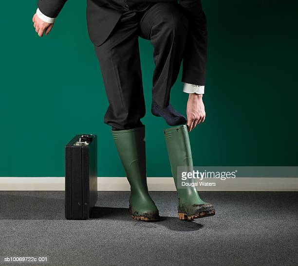 Businessman putting on galoshes, low section