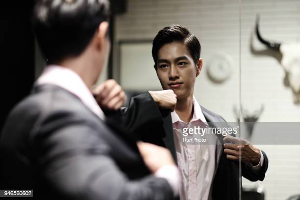 businessman putting on jacket in front of mirror - giacca da abito foto e immagini stock