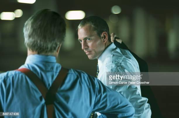 Businessman putting on jacket listening to mature businessman.