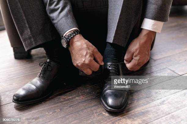 businessman putting on shoes, tying shoelace - tie stock pictures, royalty-free photos & images