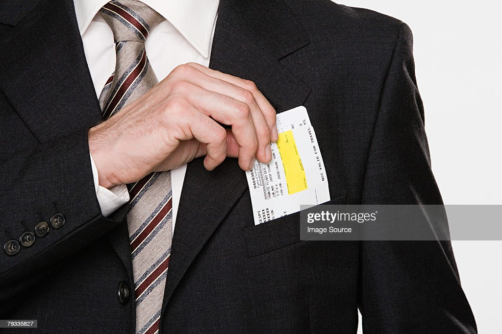 Businessman putting tickets in his pocket : Stock Photo
