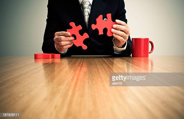 Businessman putting together jigsaw puzzle