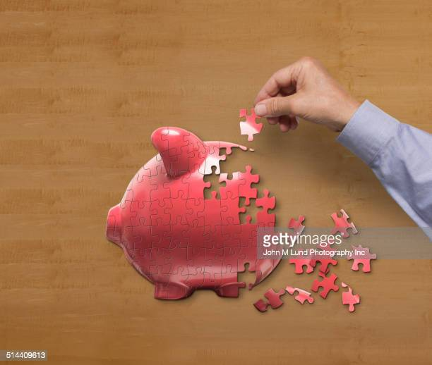 Businessman putting together piggy bank puzzle on desk