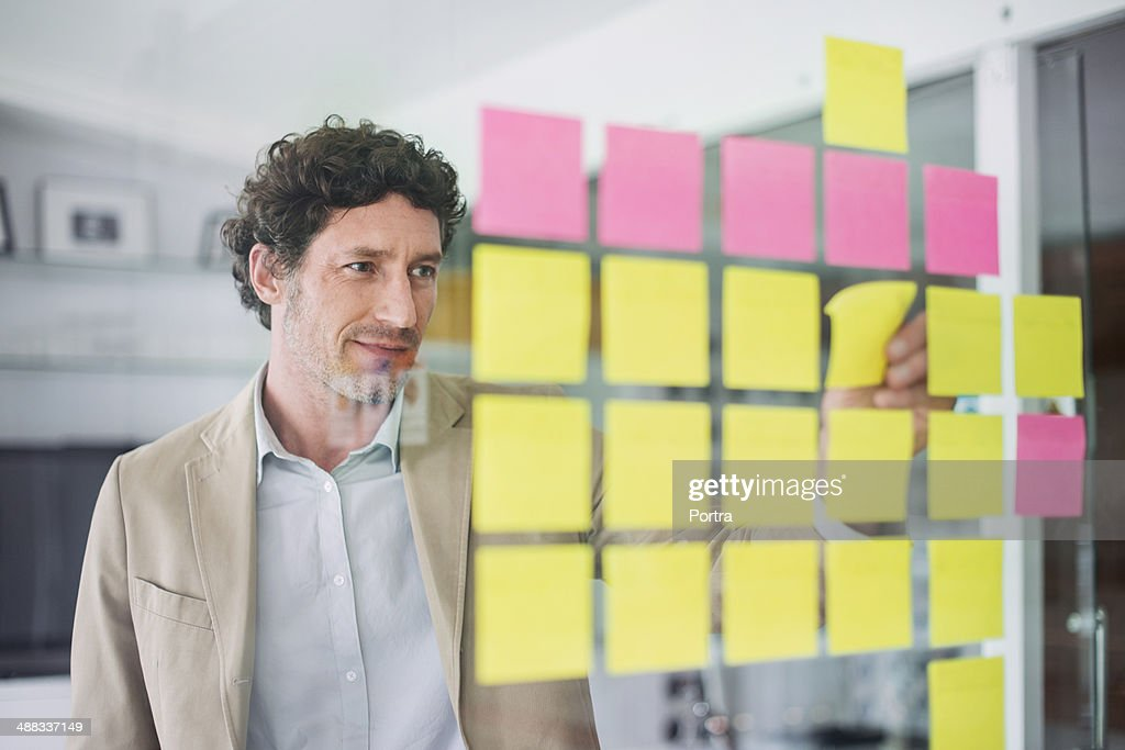 Businessman putting up stickers : Stock Photo