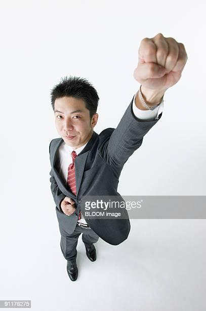 businessman raising fist, high angle view, studio shot - ガッツポーズ ストックフォトと画像