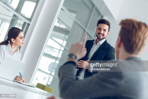 Businessman raising hand, asking question in business meeting