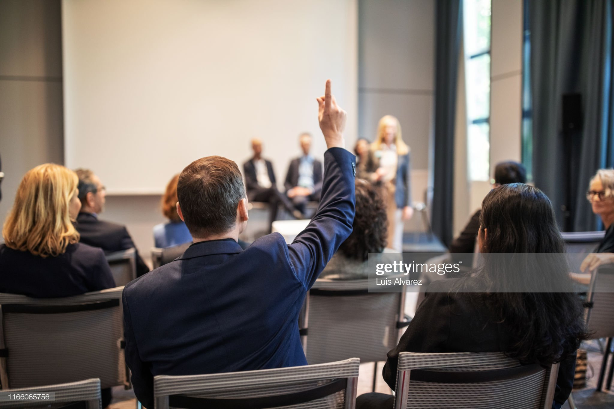 Businessman raising hand to ask question in seminar : Photo