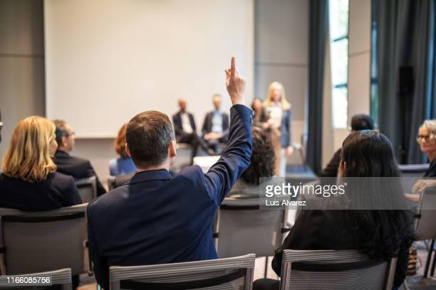 businessman raising hand to ask question in seminar - domanda e risposta foto e immagini stock