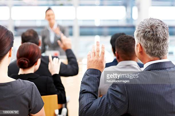 Businessman Raising His Hand at a Conference