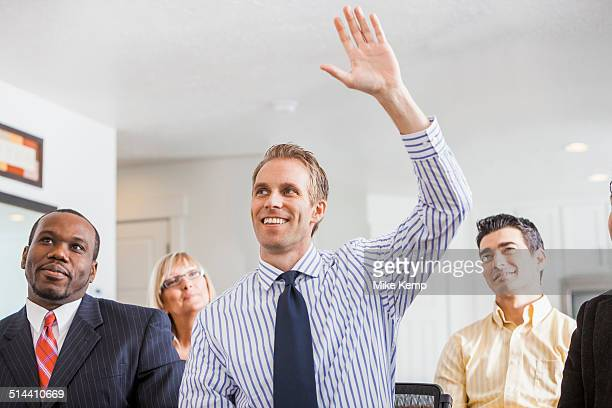 Businessman raising his hand in office