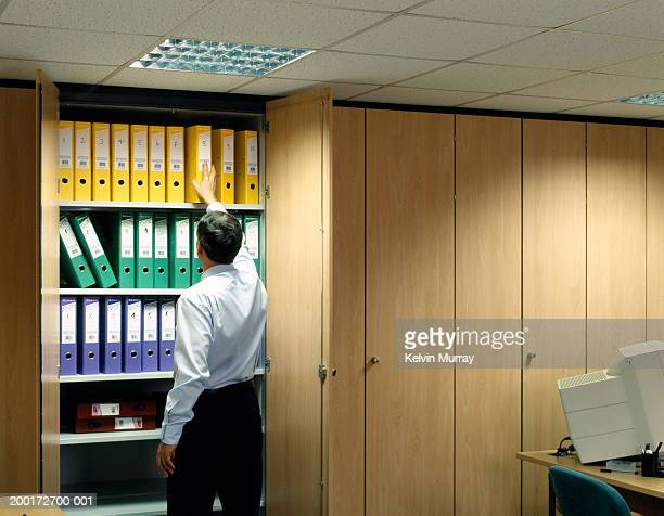 Businessman reaching for file in cupboard, rear view