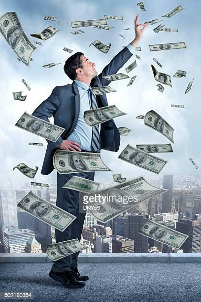 ビジネスマンに達するとお金を空から落ちています。