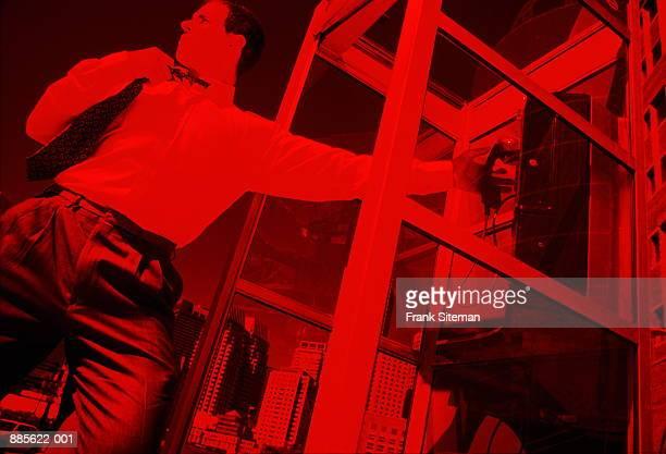 businessman reaching for public telephone (red tone) - mid section fotografías e imágenes de stock