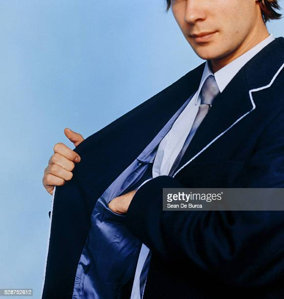 Businessman Reaching into His Inside Pocket