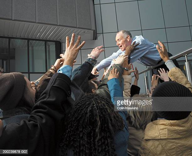 businessman reaching out to crowd of people - ヒステリー ストックフォトと画像