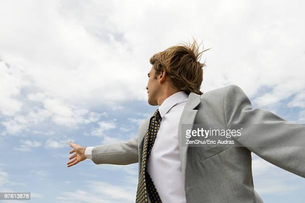 businessman reaching towards sky - só homens jovens imagens e fotografias de stock