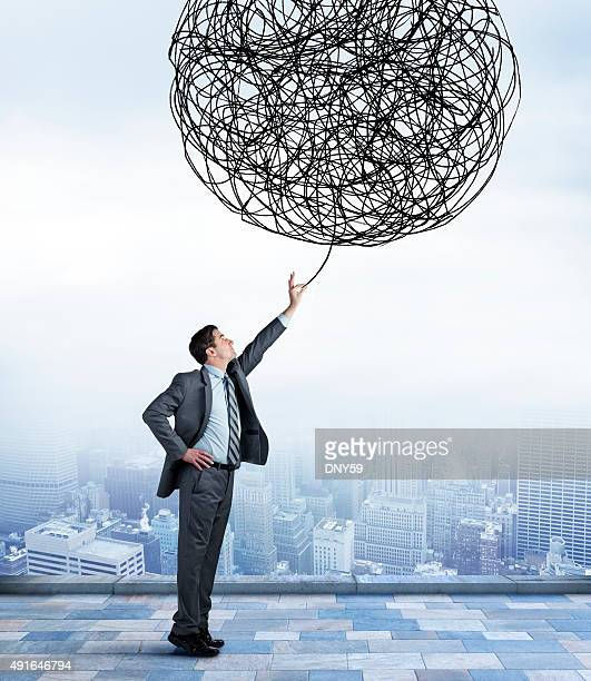 Businessman Reaching Up To Undo Tangled Ball
