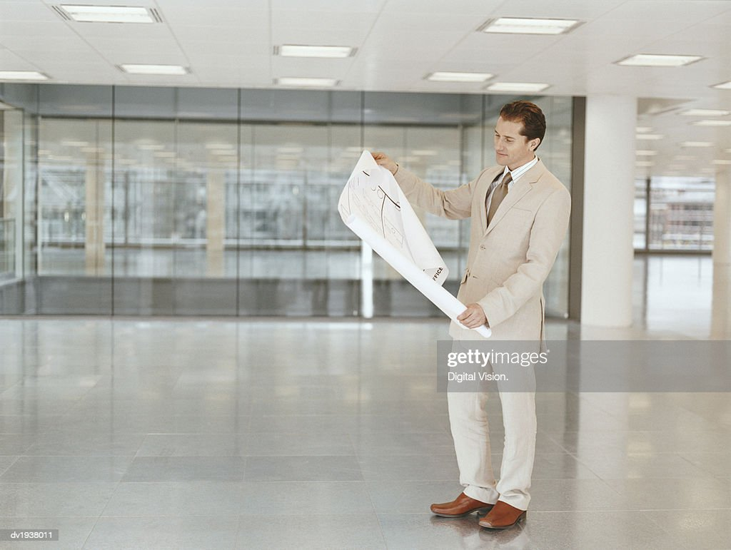 Businessman Reading a Blueprint in a Lobby : Stock Photo