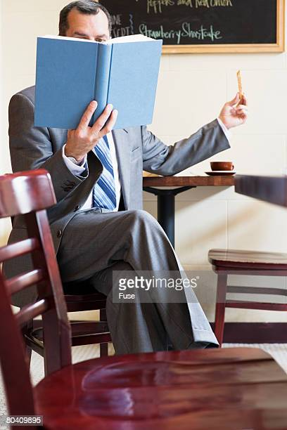 Businessman Reading a Book in Cafe