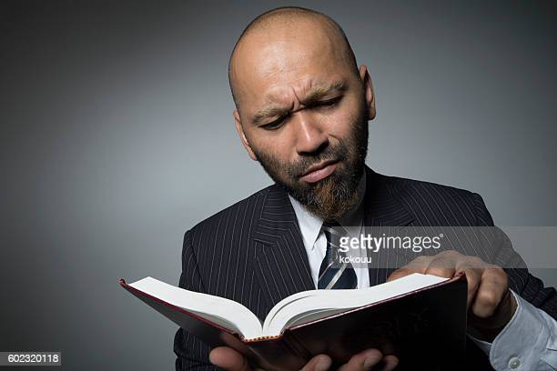 Businessman reading a book with a serious face.