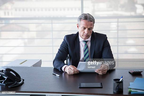 Businessman reading a contract at his desk