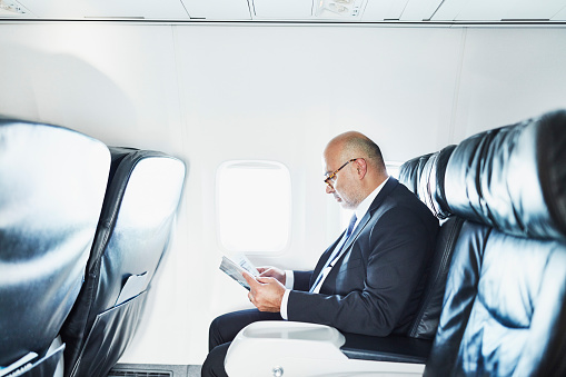 Businessman reading a magazine while traveling on airplane on business trip - gettyimageskorea