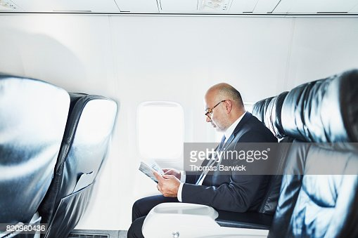Businessman reading a magazine while traveling on airplane on business trip