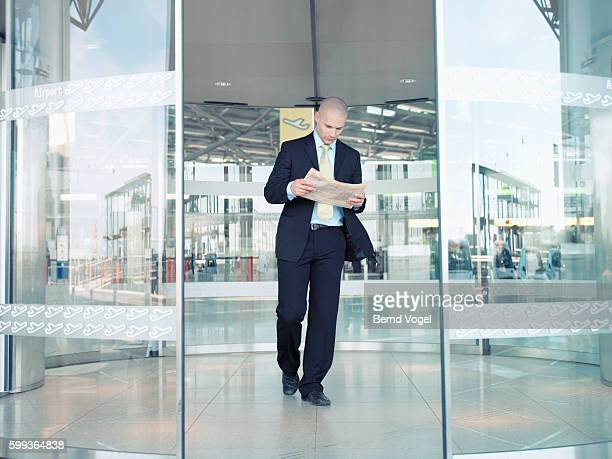 Businessman reading a newspaper as he leaves an airport