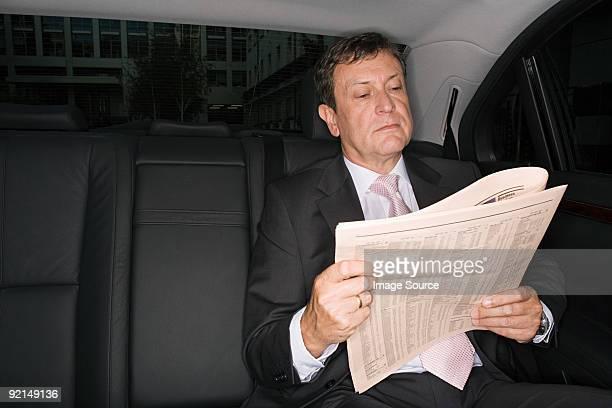 Businessman reading a newspaper in car