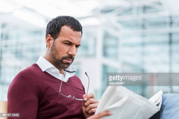 businessman reading a newspaper in waiting hall - resting stock pictures, royalty-free photos & images