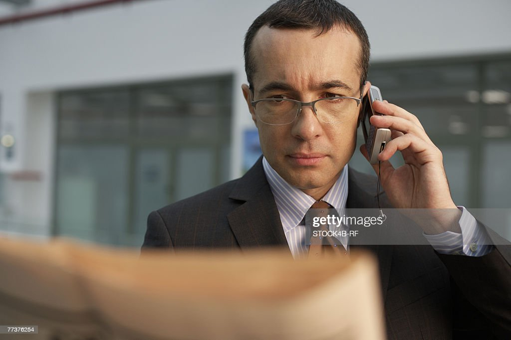 Businessman reading a newspaper while phoning with a mobile phone : Photo