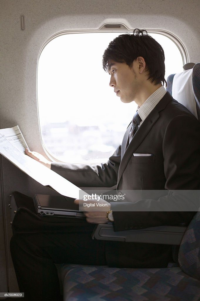 Businessman Reading a Paper on a Train : Stock Photo