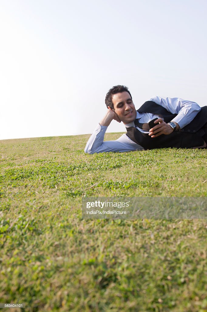 Businessman reading an sms on a mobile phone , INDIA , DELHI : Stock Photo