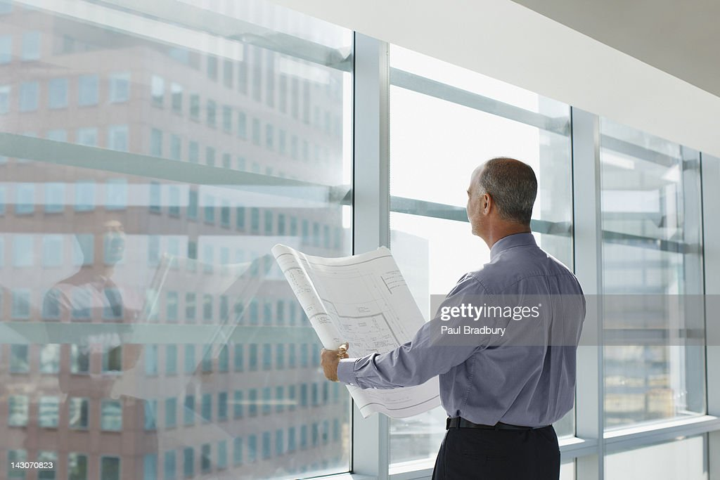 Businessman reading blueprint in office : Stock Photo