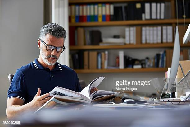 Businessman reading book at desk