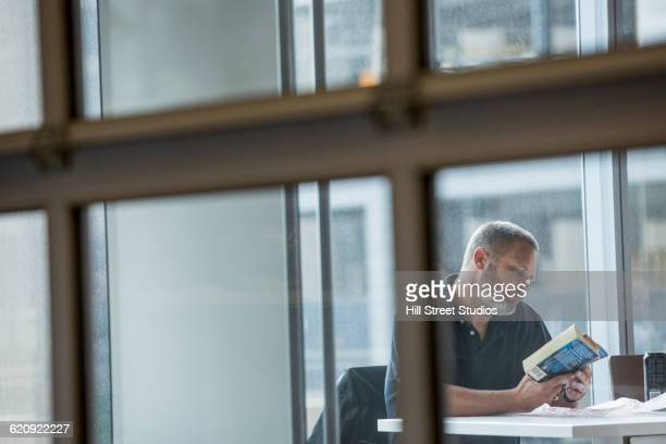 Businessman reading book at lunch