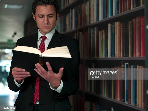 Businessman reading book in library