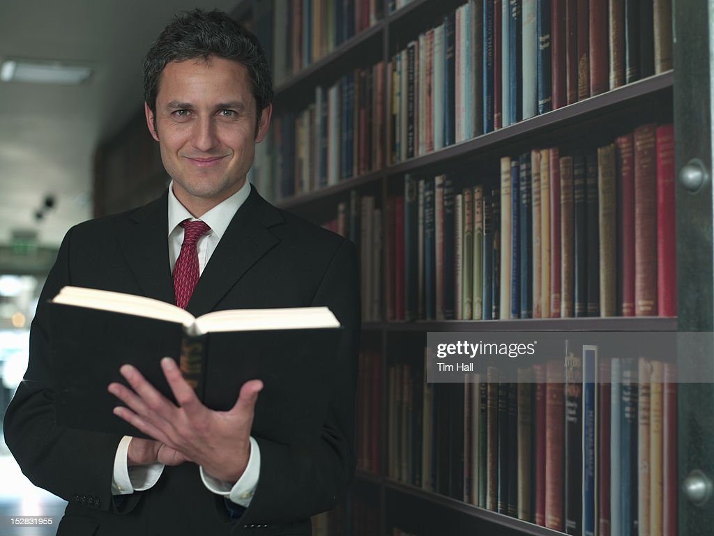 Businessman reading book in library : Stock Photo