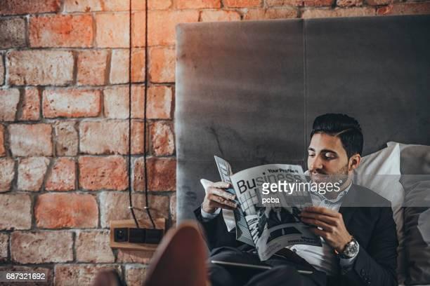 Geschäftsmann Lesung Wirtschaftsmagazin in Hotelzimmer