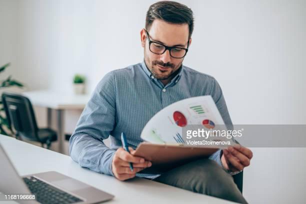 zakenman lezing document bij bureau in kantoor - overzicht stockfoto's en -beelden