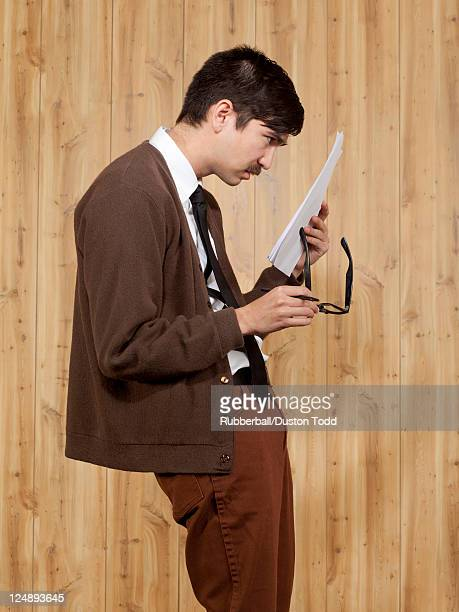 businessman reading document in office - myopia stock photos and pictures